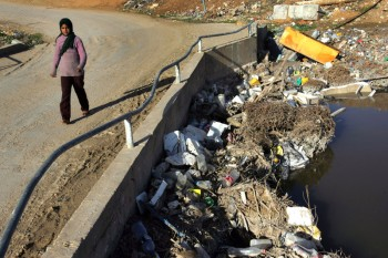 UMBETIN, ISRAEL - JANUARY 10: A Bedouin Arab girl walks barefoot across a bridge over the heavily polluted Nahal Hebron stream, laden with raw sewage, toxic industrial waste and dumped rubbish, as it passes January 10, 2007 through the unrecognized Bedouin Arab village of Umbatin in Israel's Negev desert. Living on the edge of modern Israeli society in unrecognized villages amongst the industrial parks and near the Jewish communities on land they lay claim to, many of the Negev Bedouins suffer from malignant, genetic and respiratory diseases. They also have the highest infant mortality rate in Israel. (Photo by David Silverman/Getty Images) Industrialization Threatens Traditional Bedouin Lifestyle. Photographer. Encyclopædia Britannica ImageQuest. Web. 24 Jan 2014.